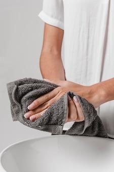 Person, die ihre hände auf einem handtuch trocknet