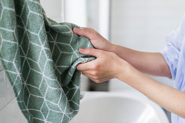 Person, die ihre hände nach dem waschen mit einem handtuch trocknet