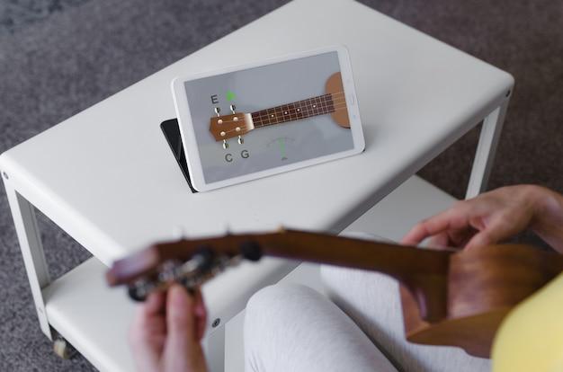 Person, die ihre ukulele mit einer app auf ihrem tablet abstimmt