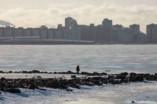 Person, die im eisigen seeufer des finnischen golfs gegenüber einem bezirk mit wolkenkratzern im winter sankt petersburg, russland steht.