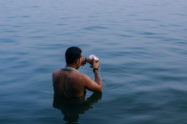 Person, die im wasser steht, während die kupferschale in indien geleert wird