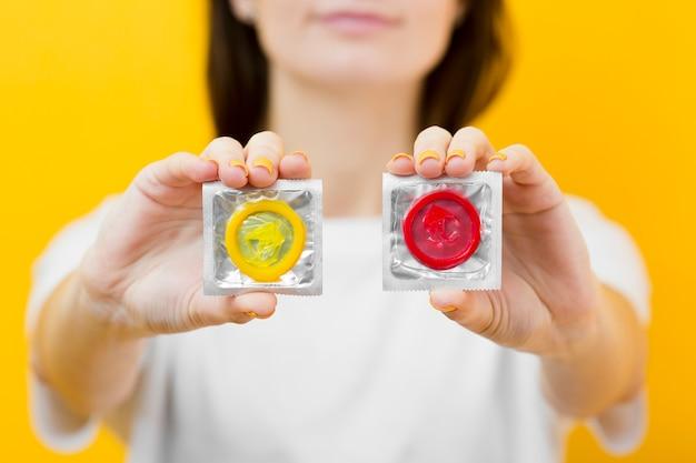 Person, die in den händen zwei kondome hält