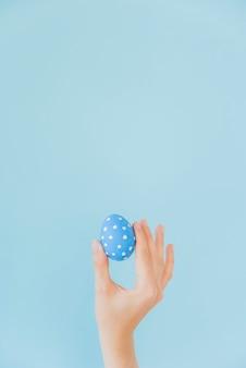 Person, die in der hand blaues osterei hält