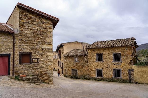Person, die in einer engen straße einer mittelalterlichen altstadt aus stein geht. horcajuelo madrid. spanien.
