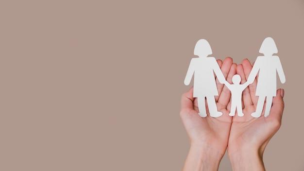 Person, die in händen niedliche papierfamilie mit kopienraum hält