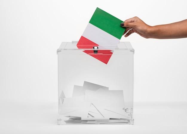 Person, die italien-flaggenkarte in wahlurne setzt