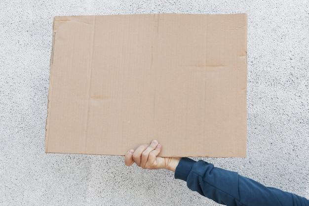 Person, die kartonplakat mit platz für inschrift hält, rassismusstreik stoppen, für defund polizei protestieren, hand mit fahne gegen weißen hintergrund.