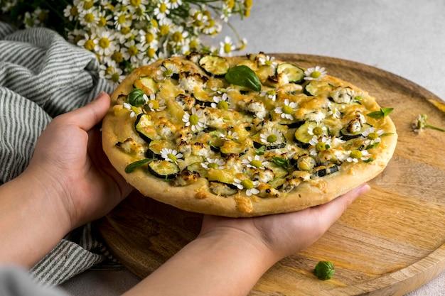 Person, die köstliche gekochte pizza mit bouquet von kamillenblüten hält