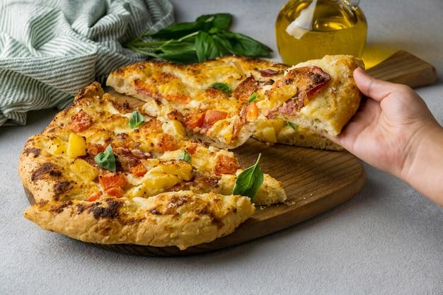 Person, die köstliches pizzastück greift