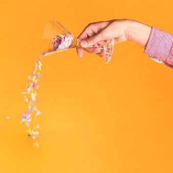 Person, die konfettis von einem glas verschüttet