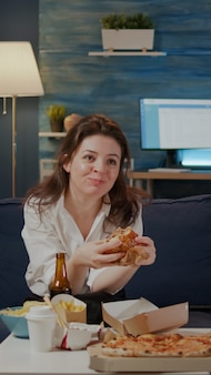Person, die leckeren hamburger und pommes im wohnzimmer isst
