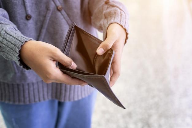 Person, die leere schwarze geldbörse überprüft