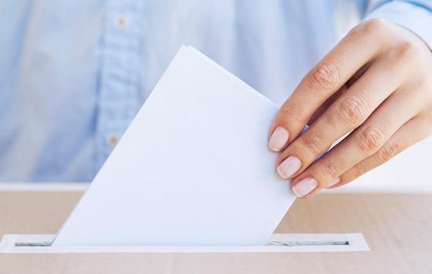 Person, die leeren stimmzettel in eine kastennahaufnahme einsetzt