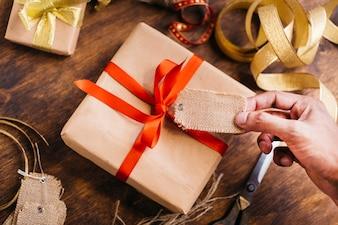 Person, die Marke über Geschenkbox hält
