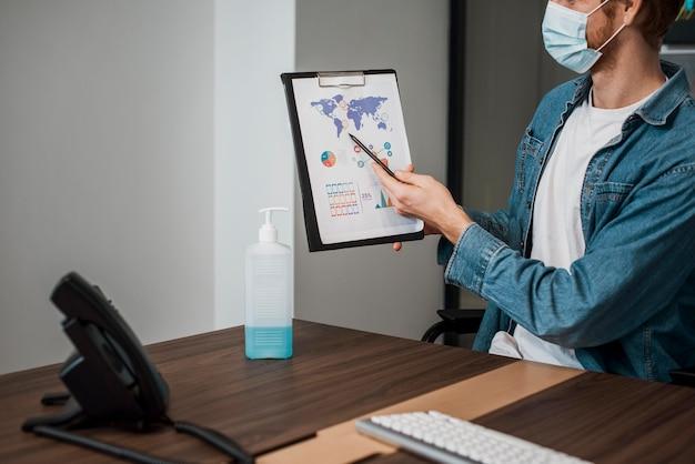 Person, die medizinische maske trägt und eine zwischenablage zeigt