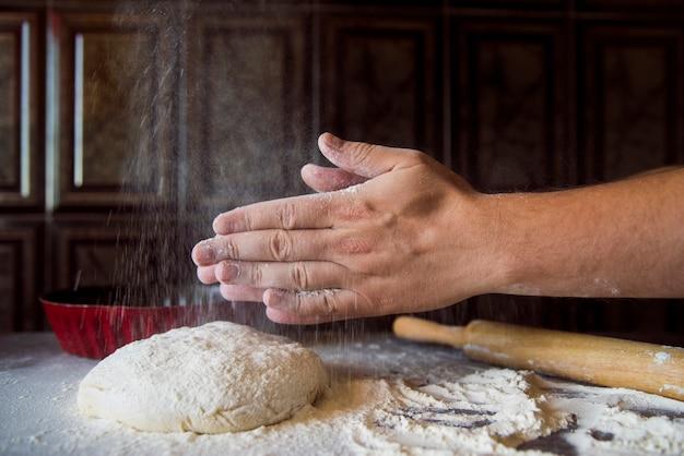 Person, die mehl aus seinen händen heraus rüttelt