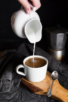 Person, die mil in tasse kaffee gießt