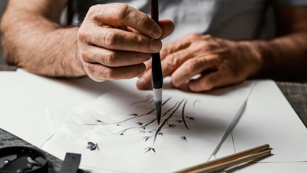 Person, die mit chinesischer tinte malt