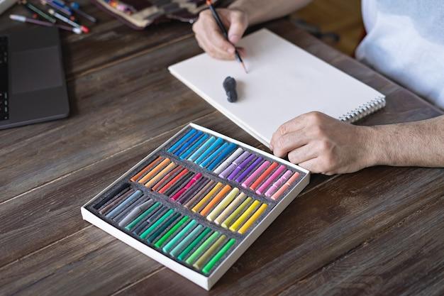 Person, die mit einer pastellkreidekreide auf einem weißen papier mit palette von pastellkreiden auf dem holztisch malt.