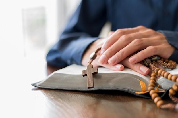 Person, die mit offenem heiligem buch und rosenkranz betet