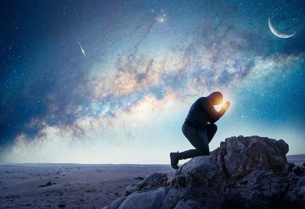 Person, die nachts unter der milchstraße und dem mond betet oder meditiert