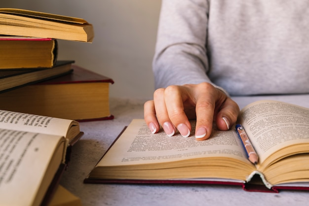 Person, die neben buchstapel studiert