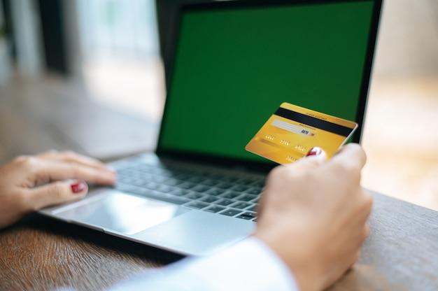 Person, die online einkauft und mit kreditkarte bezahlt