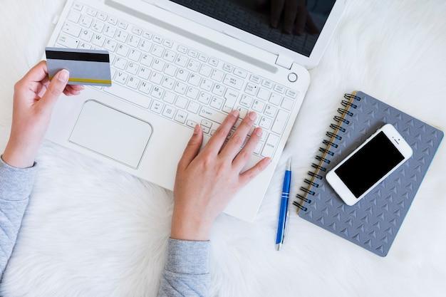 Person, die online mit einem laptop kauft