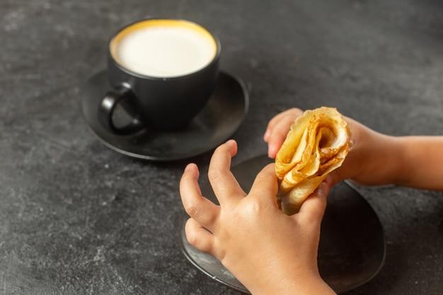 Person, die pfannkuchen isst, rollte mit tasse milch auf dunkelheit