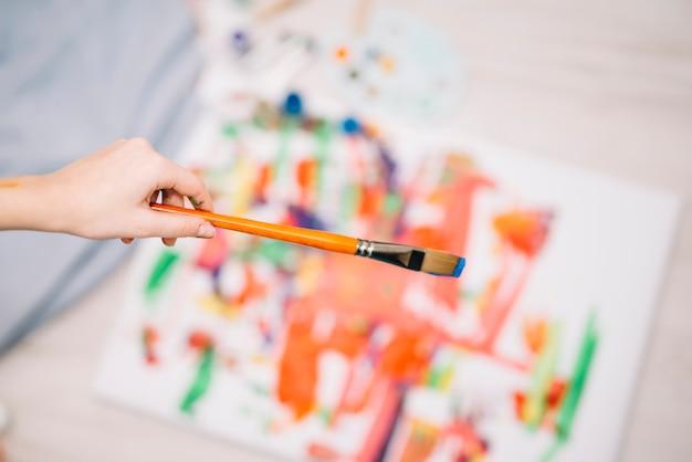 Person, die pinsel über malerei hält