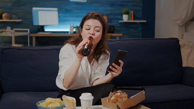 Person, die pizza isst und auf den smartphone-bildschirm schaut