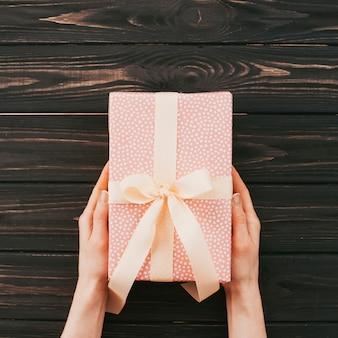 Person, die rosa geschenkbox mit band hält