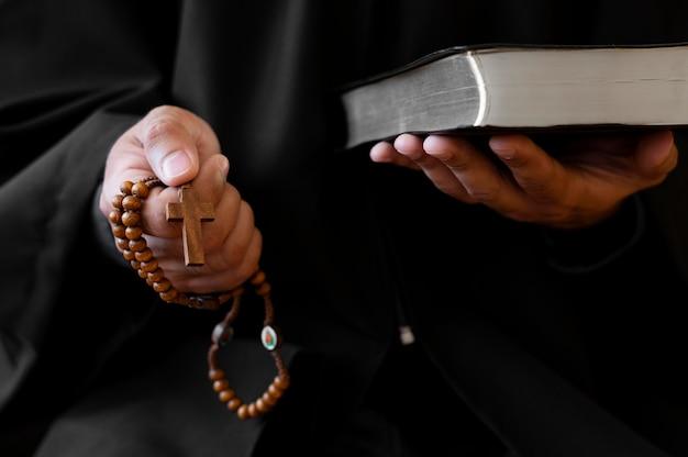 Person, die rosenkranz mit kreuz und heiligem buch hält