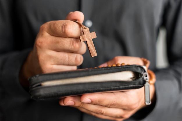 Person, die rosenkranz und heiliges buch hält