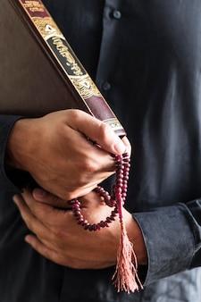 Person, die rosenkranz und religiöses buch hält