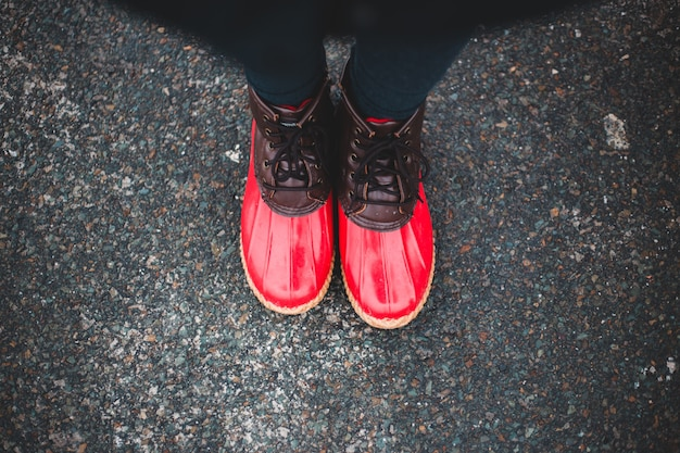 Person, die rote und schwarze sportschuhe trägt
