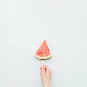 Person, die saftiges frisches wassermeloneneis am stiel hält