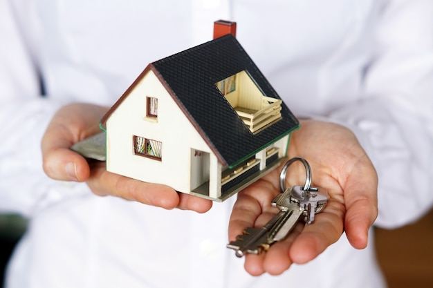 Person, die schlüssel und modellhaus hält