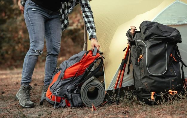 Person, die sich auf das wandern vorbereitet und rucksäcke und karemat in der nähe des zeltes auf dem campingplatz auf den boden legt ...