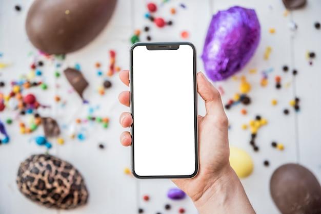 Person, die smartphone mit leerem bildschirm über ostereiern hält