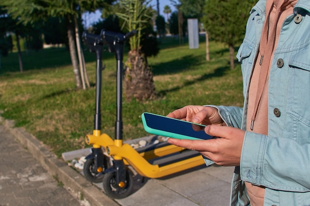 Person, die smartphone und mobile app verwendet, um einen roller für schnelles mobiles aktives fahren durch die stadt zu mieten
