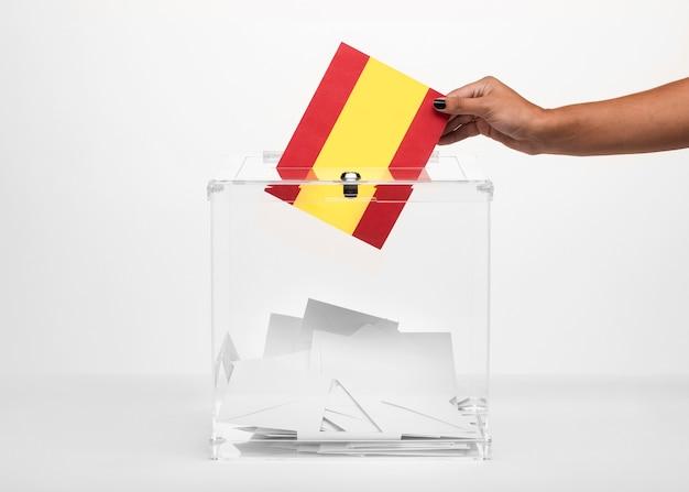Person, die spanien-flaggenkarte in wahlurne setzt