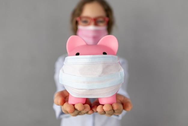 Person, die sparschwein trägt, die schutzmaske in den händen trägt