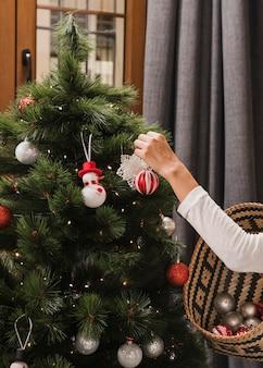 Person, die spielwaren auf den weihnachtsbaum setzt