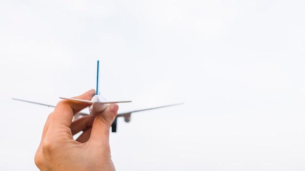 Person, die spielzeugflugzeug hält