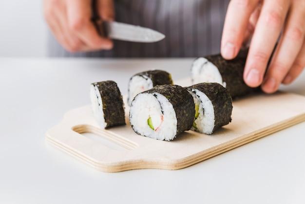 Person, die sushiverpackung auf schneidebrett schneidet
