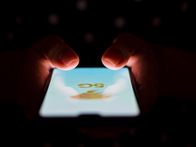 Person, die telefon im handdunkelheitshintergrund hält