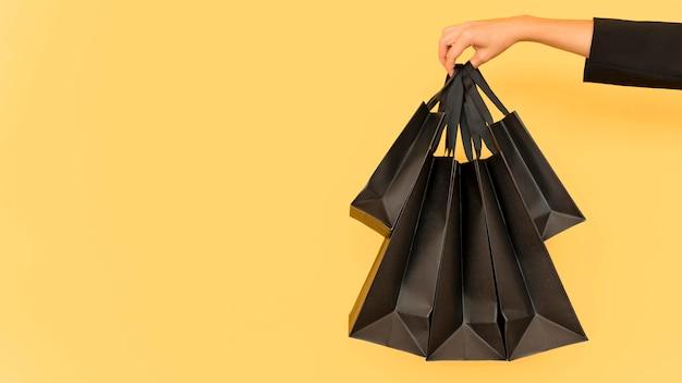 Person, die verschiedene größen der schwarzen einkaufstaschen hält