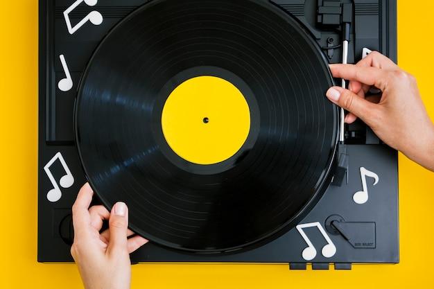 Person, die vinylaufzeichnung in spieler legt