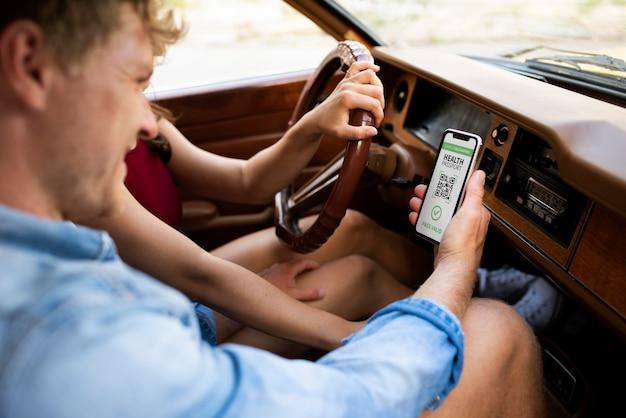 Person, die virtuellen gesundheitspass auf smartphone im auto hält